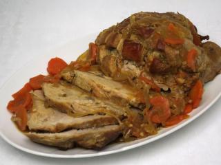 Pieczone wieprzowe mięso na cebuli z marchewką
